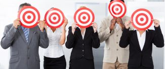 Group Of Businesspeople Holding Dartboard In Front Of Face